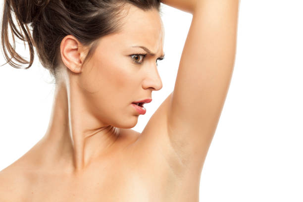 一個年輕的女人對她腋窩的氣味感到驚訝圖像檔