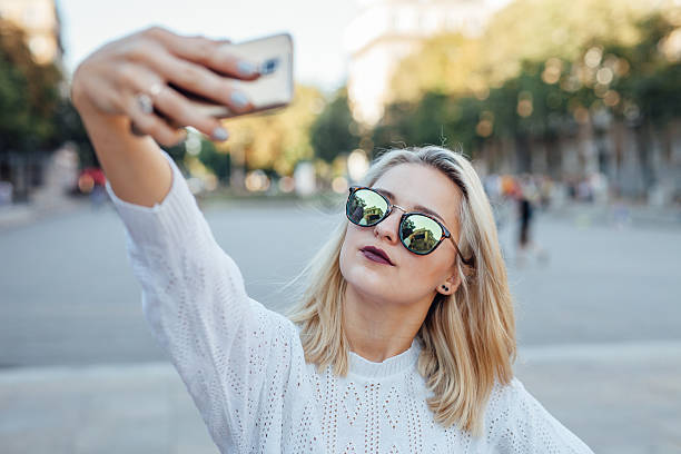 Young woman is taking a selfie by mobile phone. stock photo