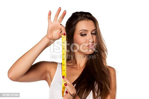 istock young woman is thrilled from the length of measuring tape 628818260