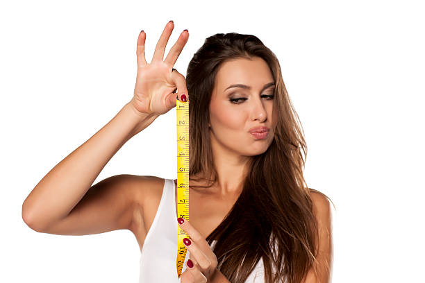 young woman is thrilled from the length of measuring tape - fotoformate stock-fotos und bilder