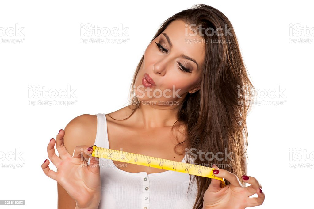 young woman is thrilled from the length of measuring tape stock photo