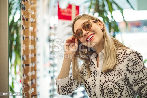 Young woman is trying on new glasses in the optics store