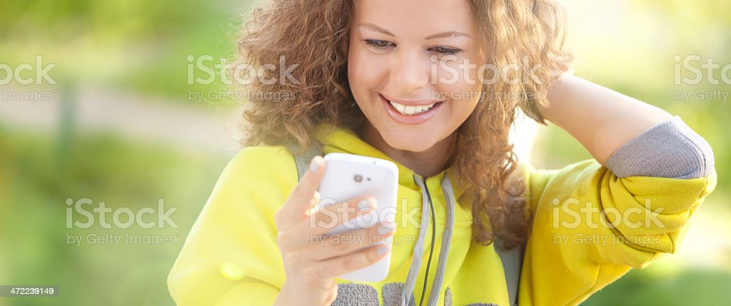 Young Woman is Viewing Photos on her Mobile Phone royalty-free stock photo