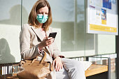 A young woman is waiting in a bus stop with a breathing mask or surgical mask in the sunlight and is using her smartphone