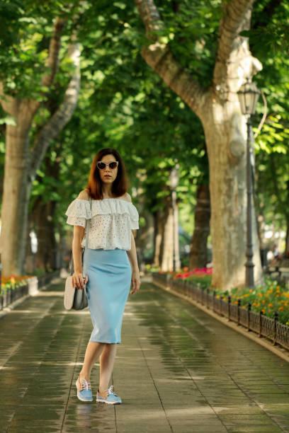 junge frau ist fuß in einem park in eine weiße bluse und eine blaue bleistiftrock. - rüschenbluse stock-fotos und bilder