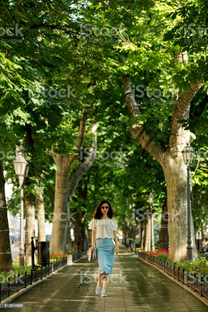 Young woman is walking in a park in a white blouse and a blue pencil skirt. stock photo