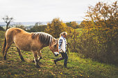 Young woman is walking with her horse in the woods on a cool autumn day