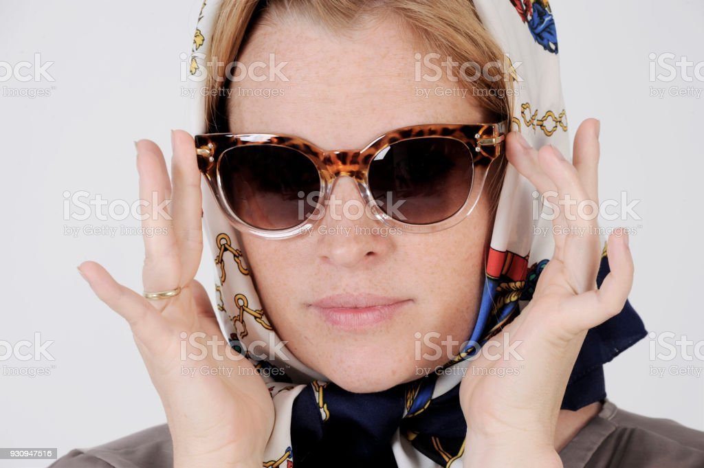 Young woman is wearing scarf and sunglasses in a Grace Kelly Style. stock photo