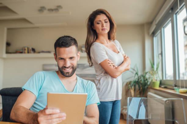 デジタル タブレットを使用して笑みを浮かべて男を見て嫉妬する若い女性 - 羨望 ストックフォトと画像