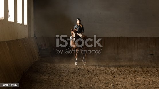 Beautiful young woman jockey doing training at riding hall