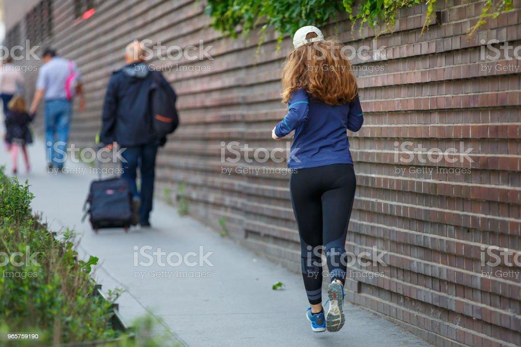 Jonge vrouw joggen langs straat in Europese stad - Royalty-free Afvallen Stockfoto