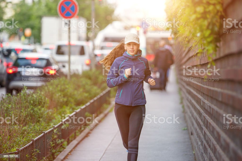 Young woman jogging along street in european city - Royalty-free Adult Stock Photo