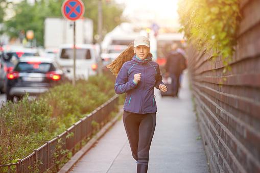 Jonge Vrouw Joggen Langs Straat In Europese Stad Stockfoto en meer beelden van Actieve levenswijze