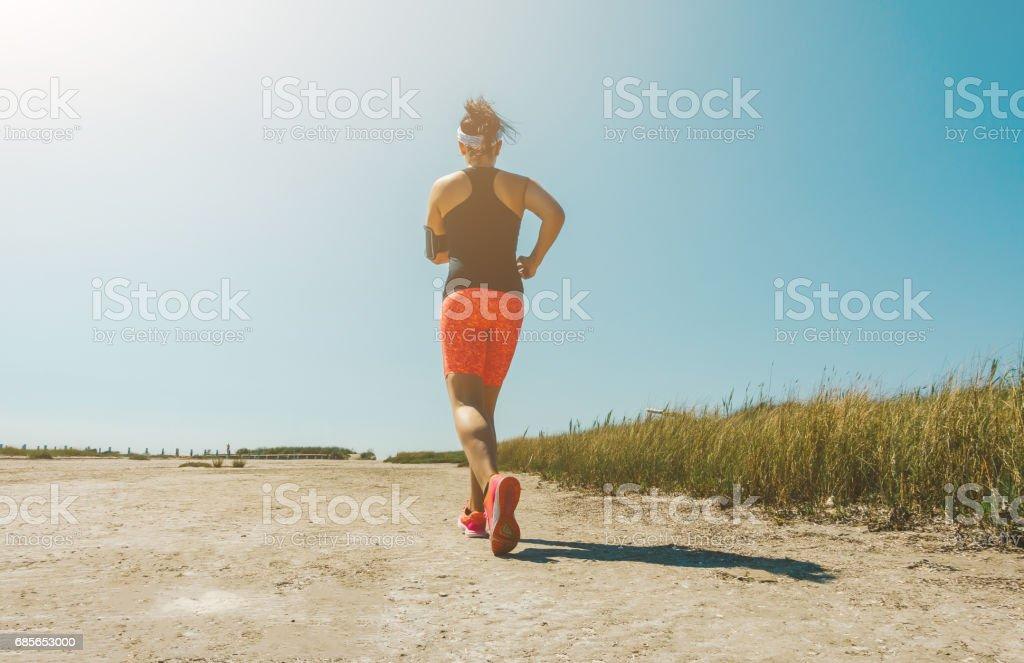 慢跑在夏天海邊越野跑的年輕女人。 概念健身和健康的生活方式 免版稅 stock photo