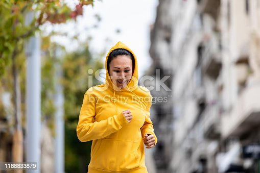 Woman jogging through the city. Woman running. Female runner jogging, training for marathon. Fit girl fitness athlete model exercising outdoor.