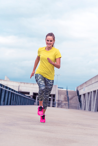 Active young woman running in urban environment