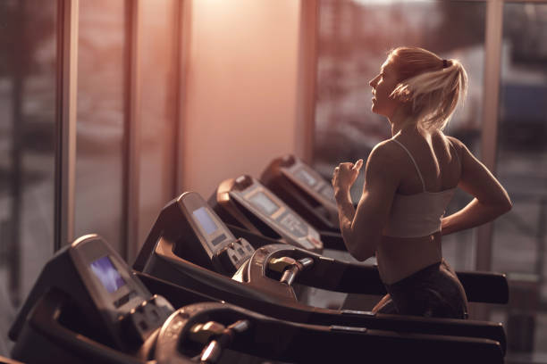 young woman jogging on a treadmill in a gym. - treadmill stock photos and pictures
