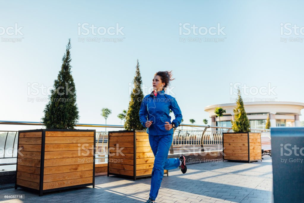Young woman wearing sweat suit jogging on empty city street in the...