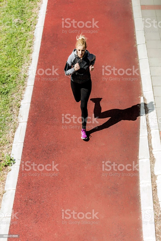 Young woman jogging on running track stock photo