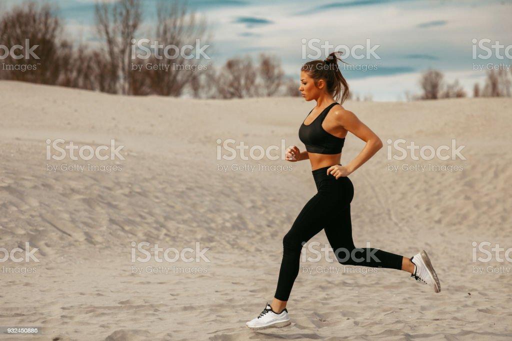 Junge Frau Joggen auf sand – Foto