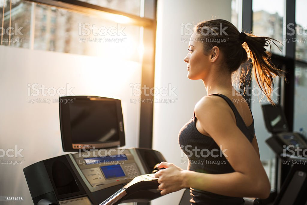 Young woman jogging on treadmill in a gym. stock photo