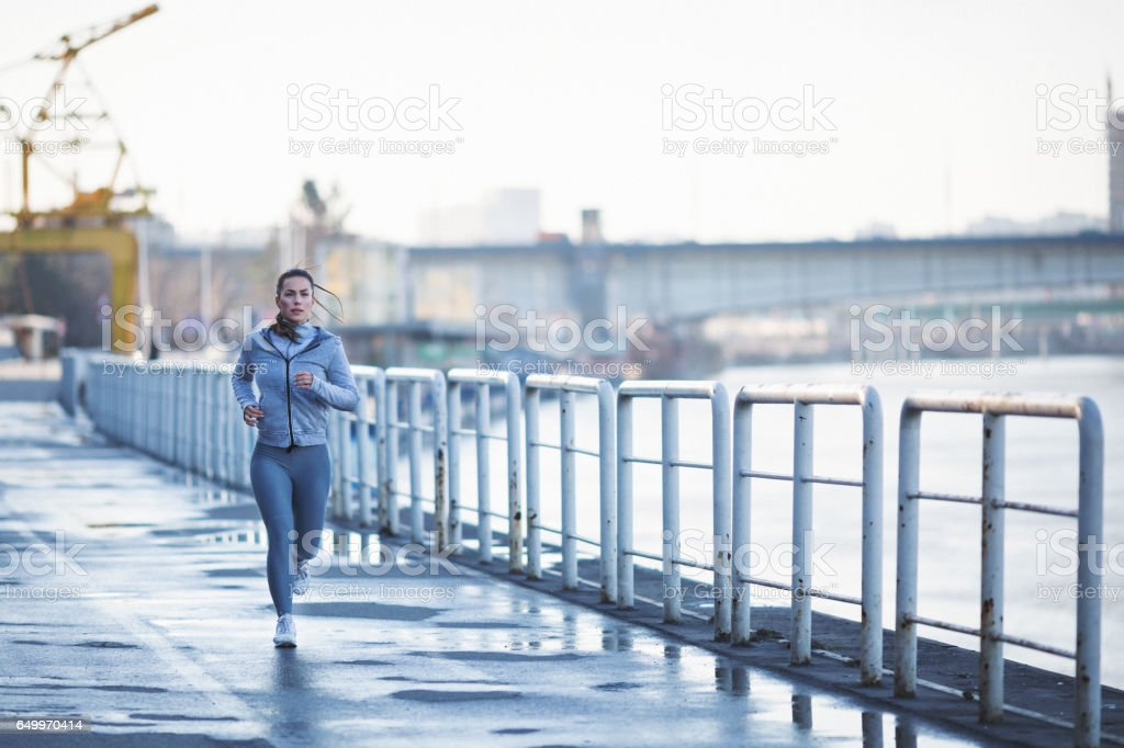 Young woman jogging outdoors by the river stock photo