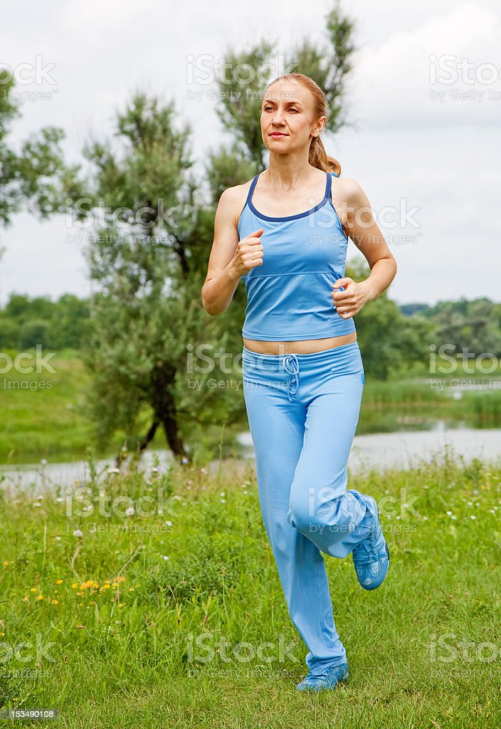 young woman jogging  the park in summer royalty-free stock photo