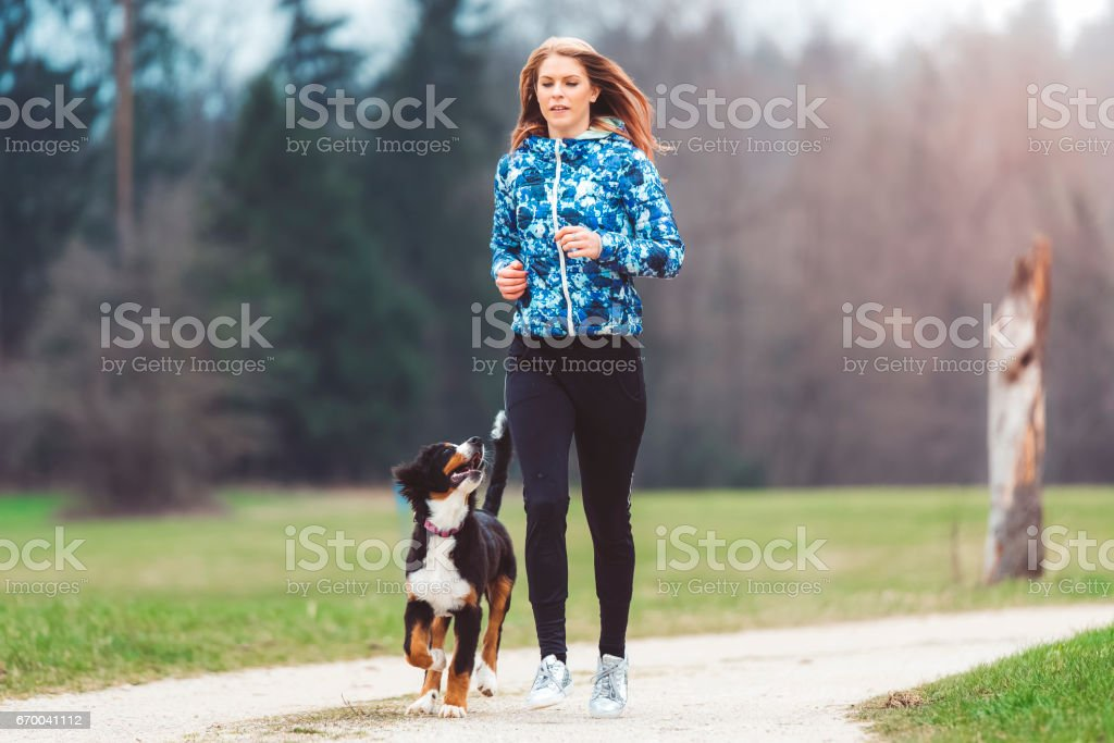 Young woman jogging with dog stock photo