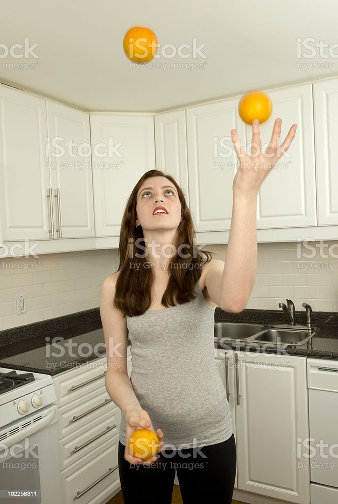 Young woman juggles three oranges royalty-free stock photo