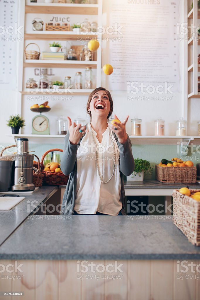 Young woman juggling with fruits at juice bar stock photo