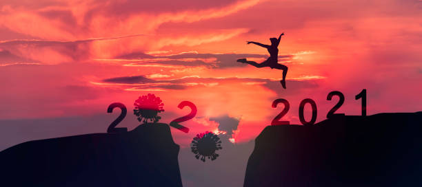 Young woman Jumping across the gap of the mountain from COVID-19 to 2021 New Year. Young woman Jumping across the gap of the mountain from COVID-19 to 2021 New Year. happy new year 2021 stock pictures, royalty-free photos & images