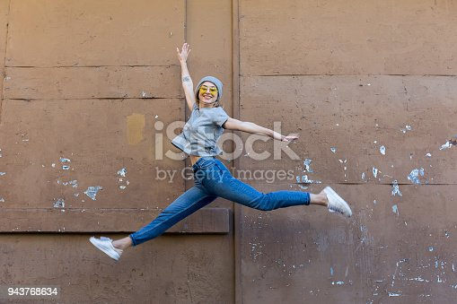 istock Young woman jumping front of wall 943768634