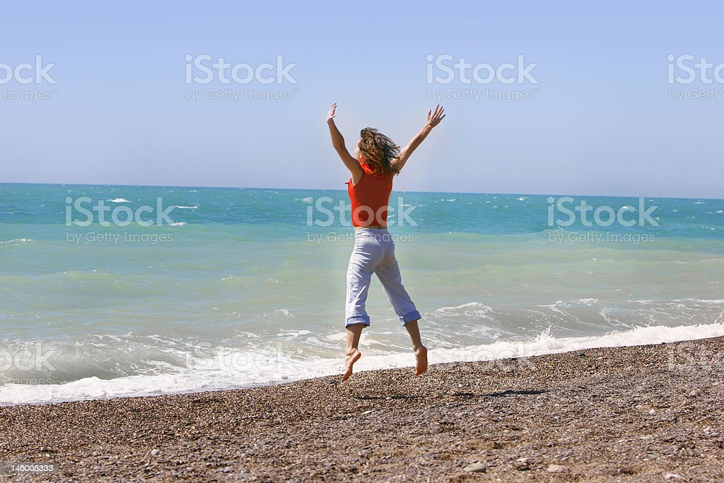Young woman jumping happily on the beach royalty-free stock photo