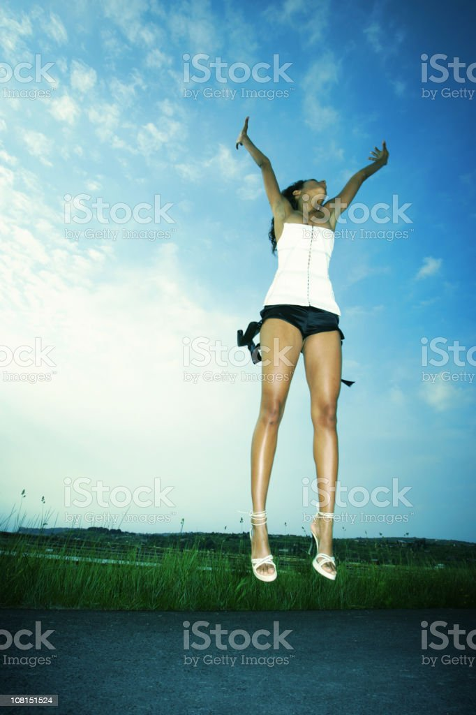 Young Woman Jumping High Above Road royalty-free stock photo