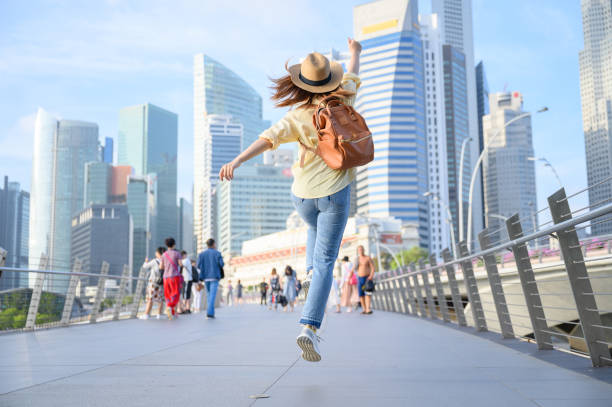 Young woman jumping in city, happiness and vacation concept stock photo