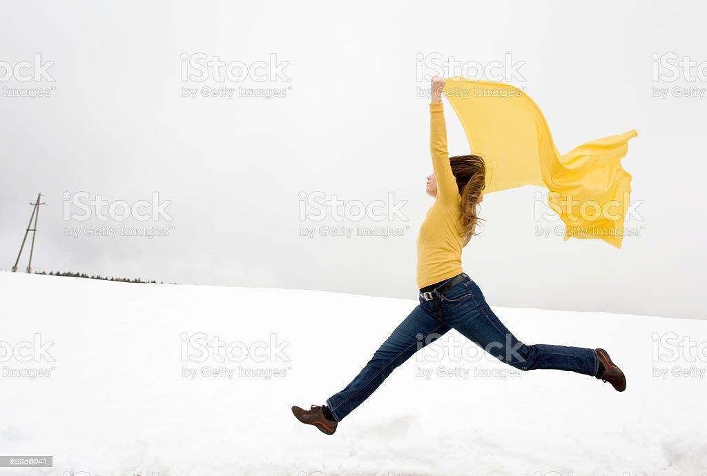 Giovane donna salto nella neve con sciarpa giallo a vento foto stock royalty-free