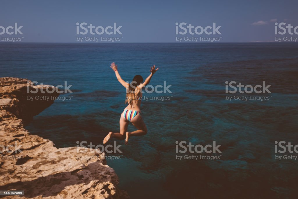 Young woman jumping off cliff and diving into blue sea stock photo