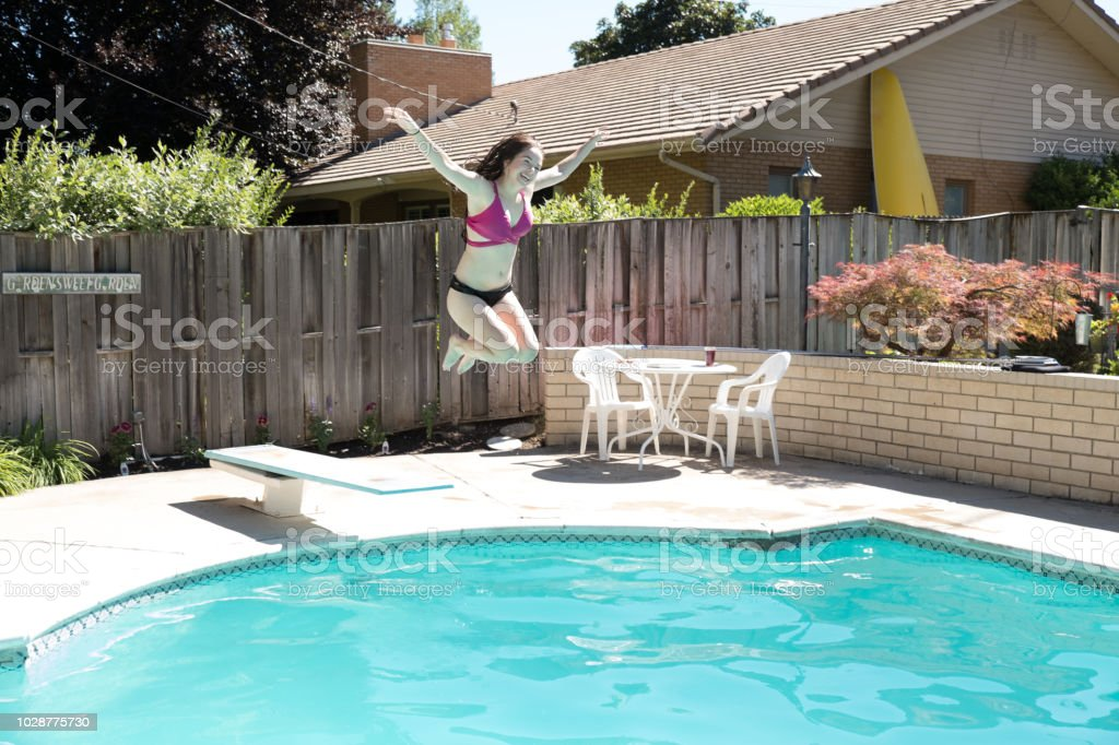 Young Woman Jumping Off Diving Board Into A Backyard ...