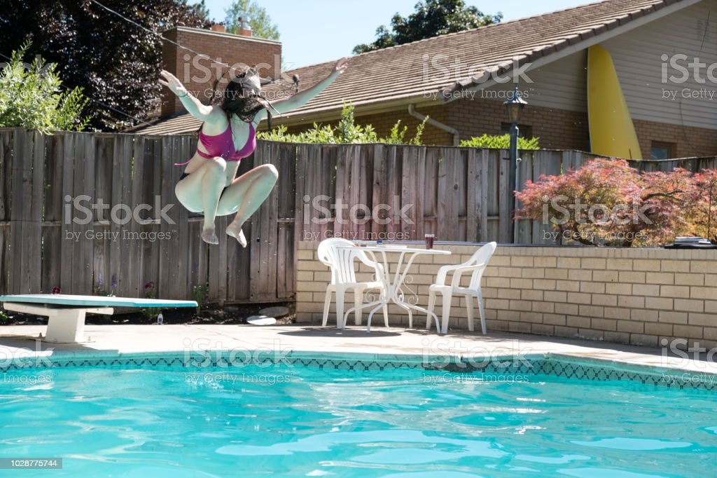Young Woman Jumping Off Diving Board Into A Backyard Swimming Pool Arms Up  In The Air Legs Tucked To Her Body Caught In Mid Air Girl In Bikini Jumps  ...