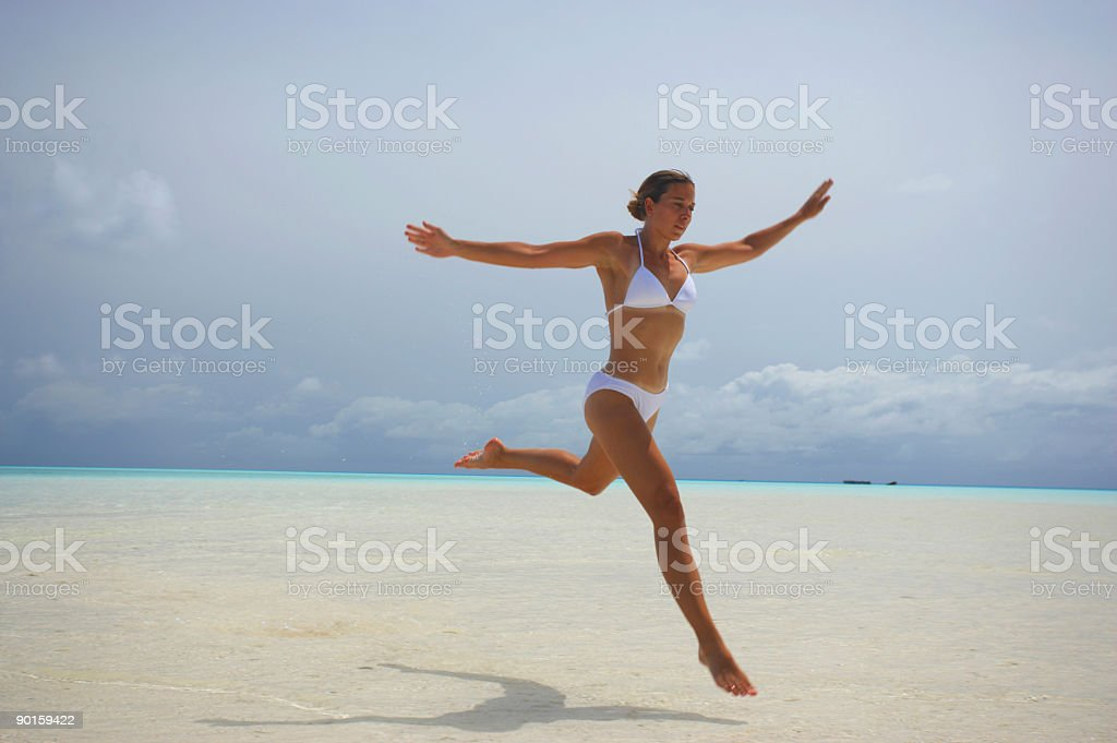 young woman jumping on beach royalty-free stock photo