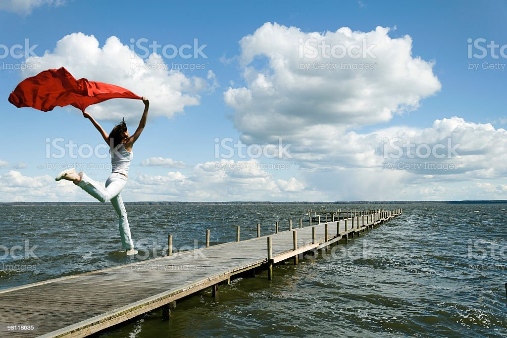 Young woman jumping on lakeside dock with red scarf royalty-free stock photo