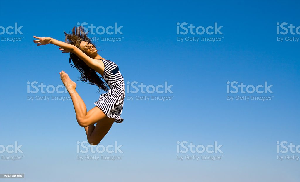 Young woman jumping on the background of blue sky stock photo
