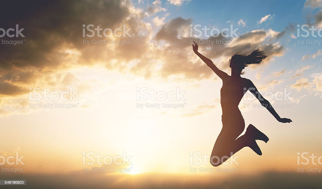 Young woman jumping outdoors at sunset stock photo