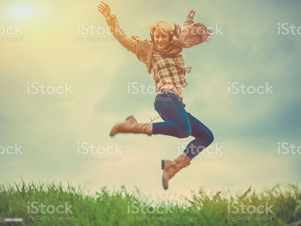 Young woman jumping outdoors stock photo