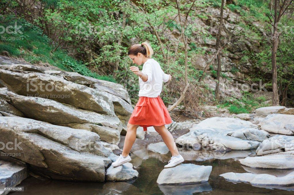 Young woman jumping over the creek photo libre de droits