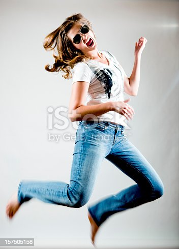 istock Young woman jumping while doing air guitar 157505158
