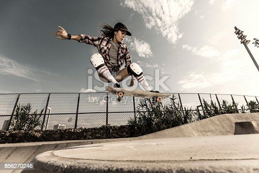 istock Young woman jumping with skateboard 856270246
