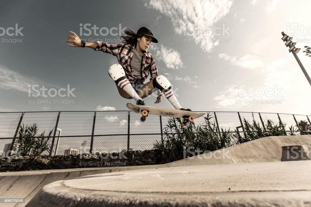 Young woman jumping with skateboard stock photo