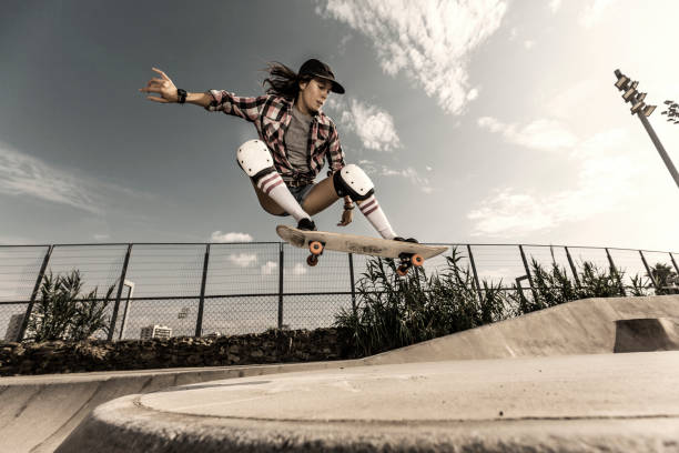 young woman jumping with skateboard - skateboard stock pictures, royalty-free photos & images