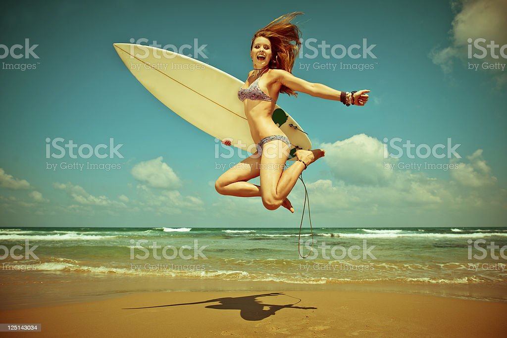 Young woman jumping with surf-board on the beach royalty-free stock photo